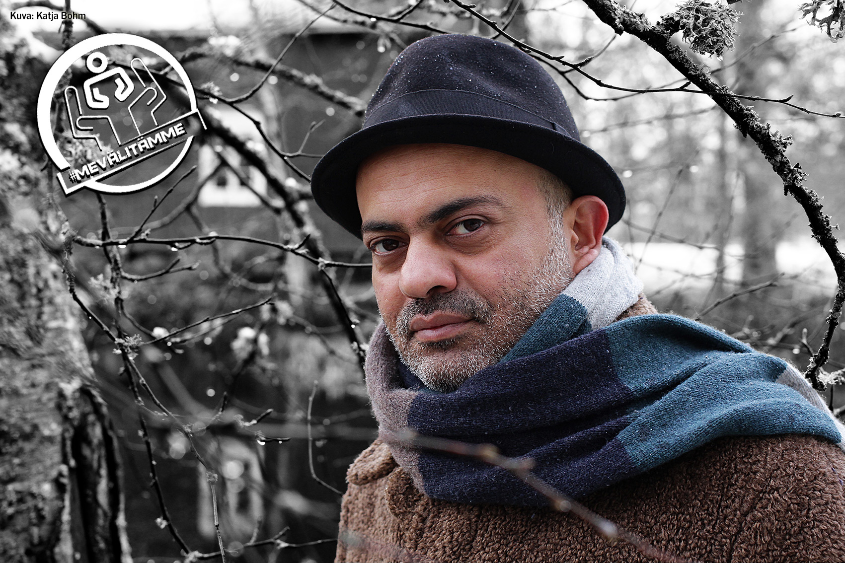 Hassan Blasim katsoo kameraan vakavin ilmein talvisen maiseman edessä. Hän on pukeutunut mustaan lierihattuun, siniseen huiviin ja ruskeaan takkiin.